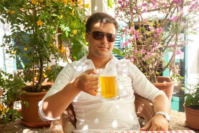 Portret van knap mens het drinken bier bij restaurant bij hete dag royalty-vrije stock foto's
