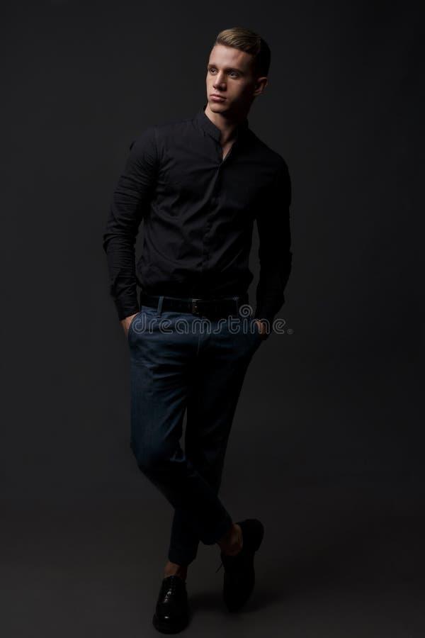 Portret van knap, mens tegen donkere achtergrond stock afbeelding