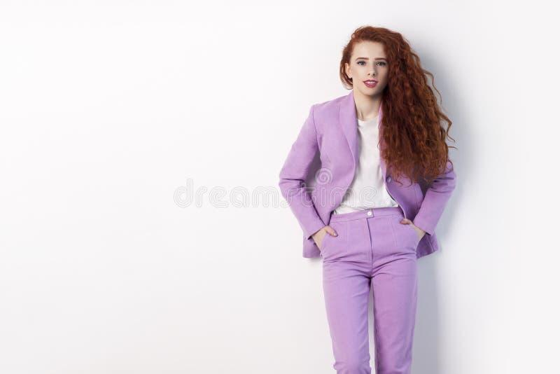 Portret van knap mooi krullend roodharige met make-up in roze kostuum die zich met handen op zakken bevinden en camera bekijken m stock fotografie
