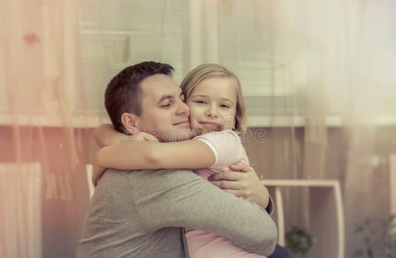 Portret van knappe, camera bekijken en vader en zijn leuke dochter die glimlachen koesteren Het concept paarfamilie is in verdrie royalty-vrije stock foto's