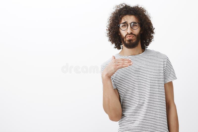Portret van knappe charmante kerel met bedgedrag, die zich over grijze achtergrond, whisteling en golvende palm bevinden terwijl royalty-vrije stock foto's