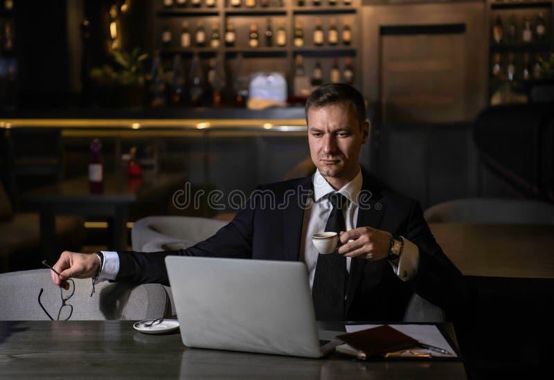 Portret van knappe elegante Kaukasische zakenman die aan zijn laptop en het drinken koffie in restaurant werken stock afbeeldingen