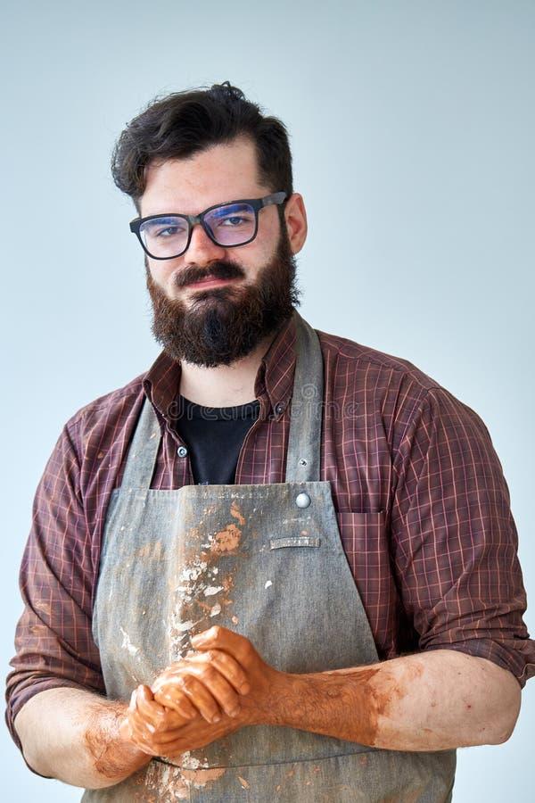 Portret van knappe jonge pottenbakker met vuile handen, close-up stock afbeelding