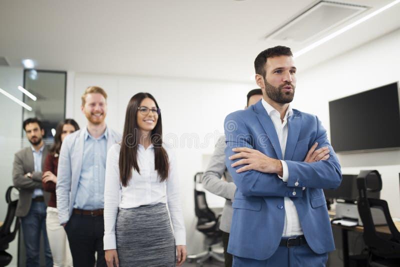 Portret van knappe jonge zakenman met zijn collega's stock afbeelding