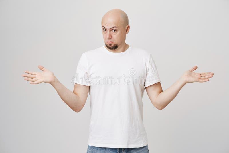 Portret van knappe kale gebaarde mens het uitspreiden handen en buigend hoofd naar en in verwarring gebrachte camera die, worden  stock fotografie