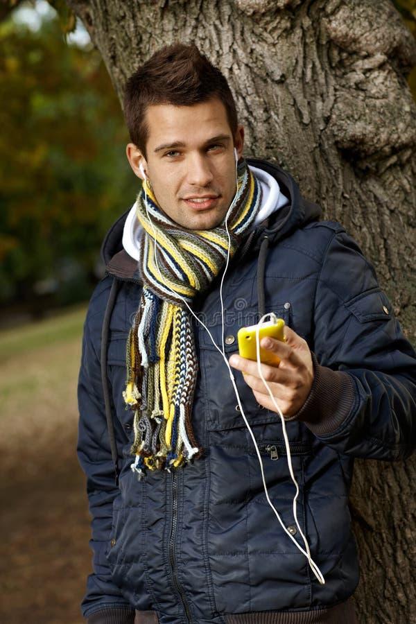 Portret van knappe kerel met mp3 speler in openlucht stock fotografie