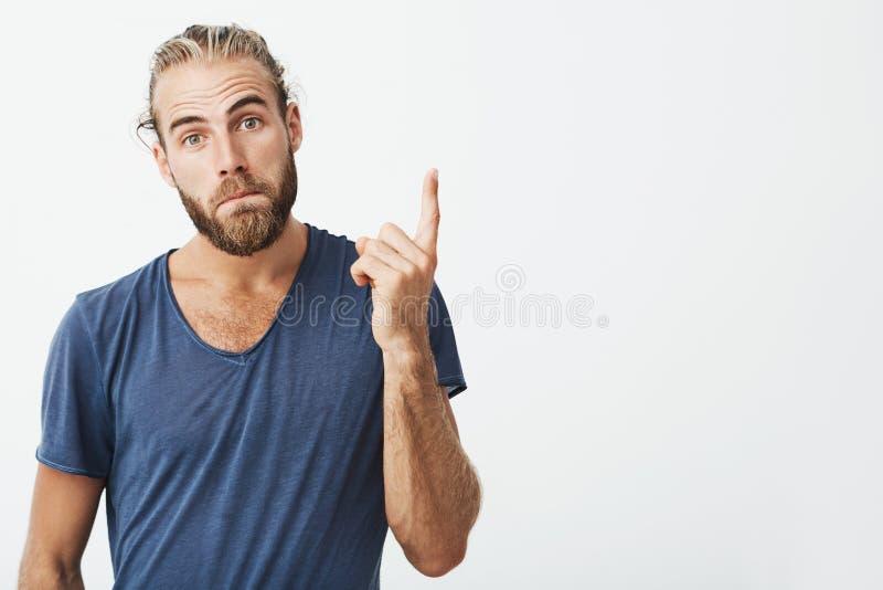 Portret van knappe mannelijke kerel met in kapsel en baard die camera bekijken, lippen achtervolgen en plaats benadrukken royalty-vrije stock foto's