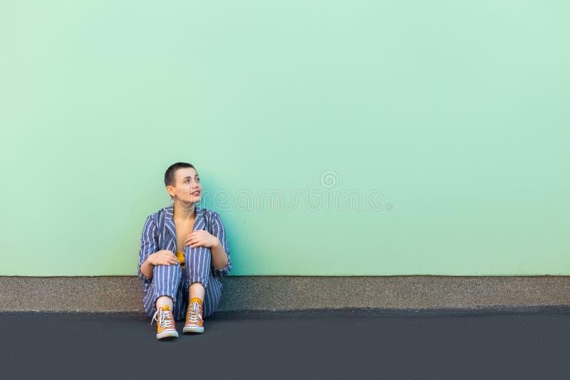 Portret van knappe mooie korte haar jonge modieuze vrouw in toevallige gestreepte kostuum zitting en het bekijken lege exemplaar  royalty-vrije stock afbeeldingen