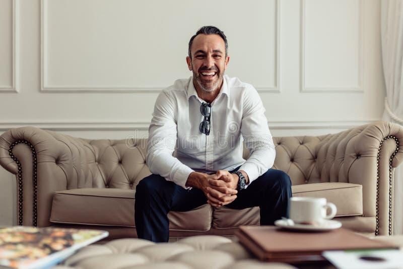 Portret van knappe rijpe zakenmanzitting op bank in hotelruimte Vrolijke CEO die in luxueuze hotelruimte blijven op zaken royalty-vrije stock foto's