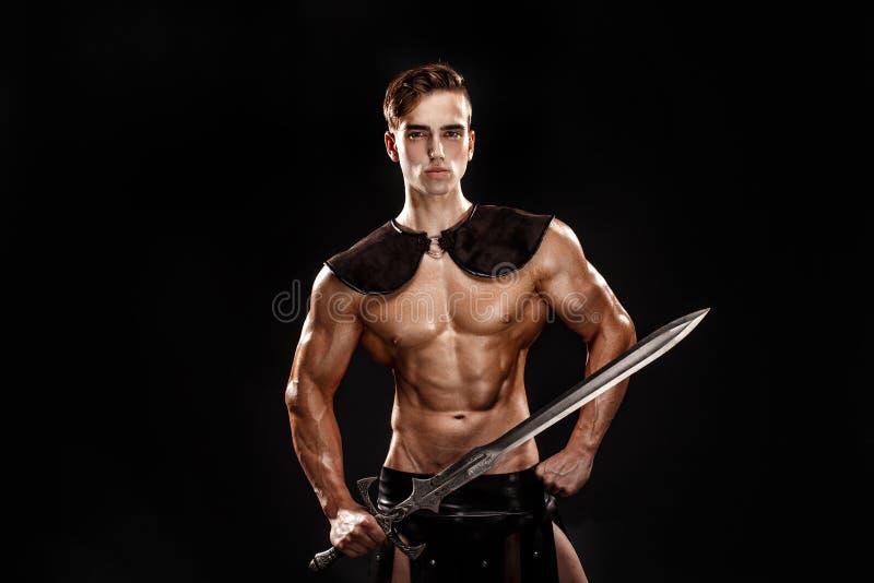 Portret van knappe spiergladiator met zwaard Geïsoleerde Het schot van de studio stock foto