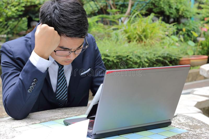 Portret van knappe zakenman die laptop bekijken en over zijn baan in het park in openlucht denken stock foto