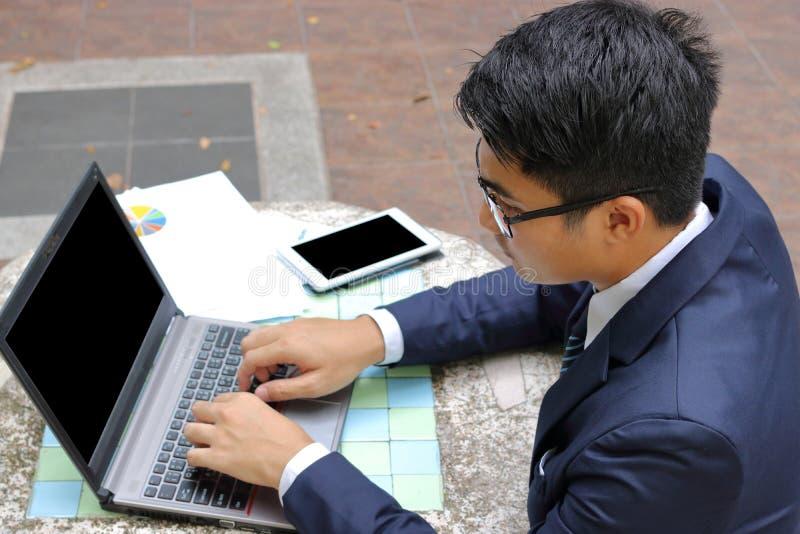 Portret van knappe zakenman die laptop computer voor zijn werk in openlucht met behulp van bij het park stock fotografie