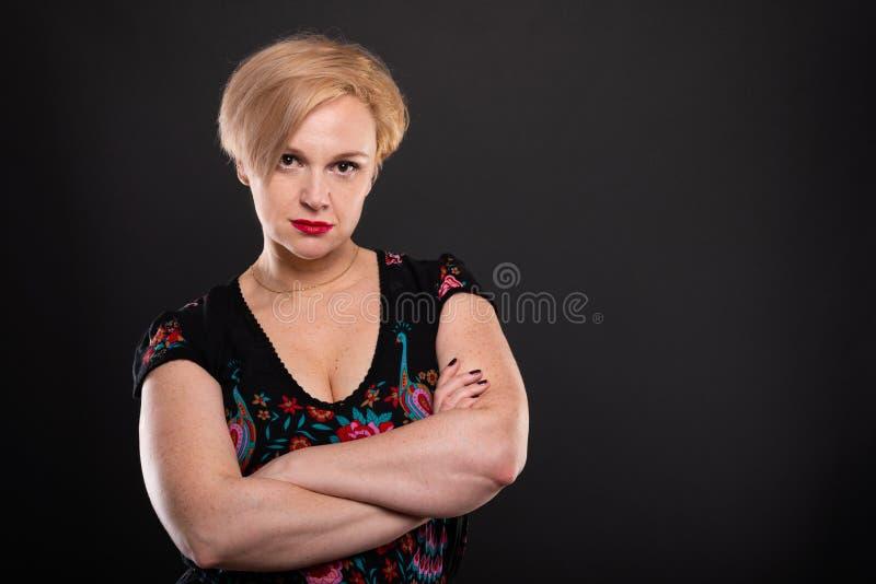 Portret van koele modieuze vrouw status met gekruiste wapens stock foto's