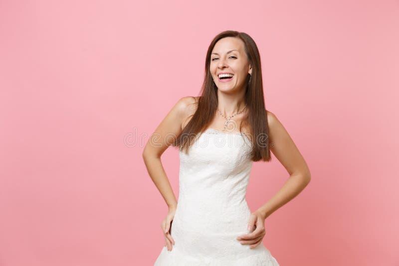 Portret van lachende gelukkige bruidvrouw in de elegante witte kleding die van het huwelijkskant zich met met de handen in de zij stock fotografie