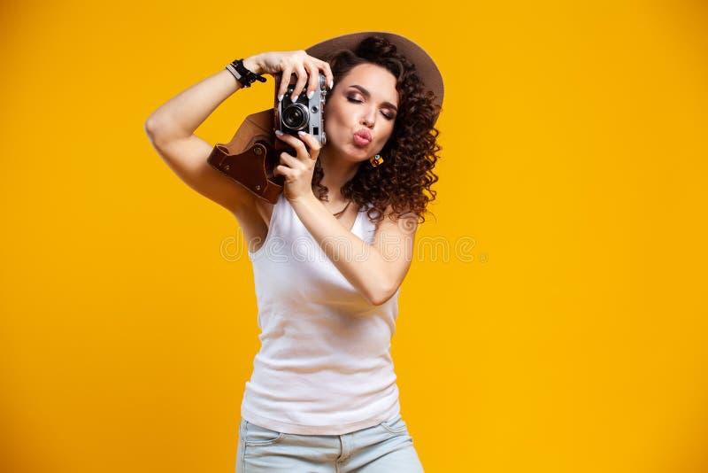 Portret van lachende jonge vrouw die beelden op retro uitstekende die fotocamera nemen op heldere gele achtergrond worden geïsole stock afbeelding