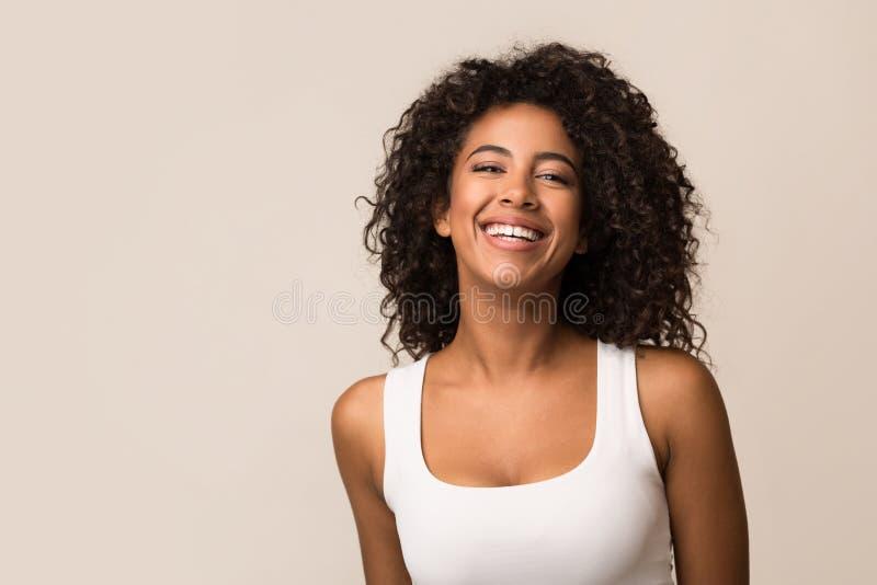 Portret van lachende jonge vrouw tegen lichte achtergrond royalty-vrije stock foto's