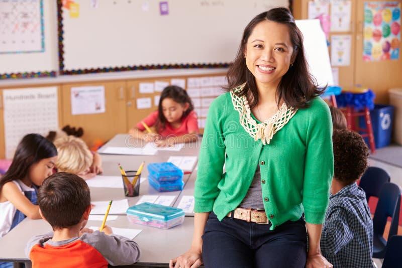 Portret van leraar in klaslokaal met basisschooljonge geitjes stock afbeeldingen