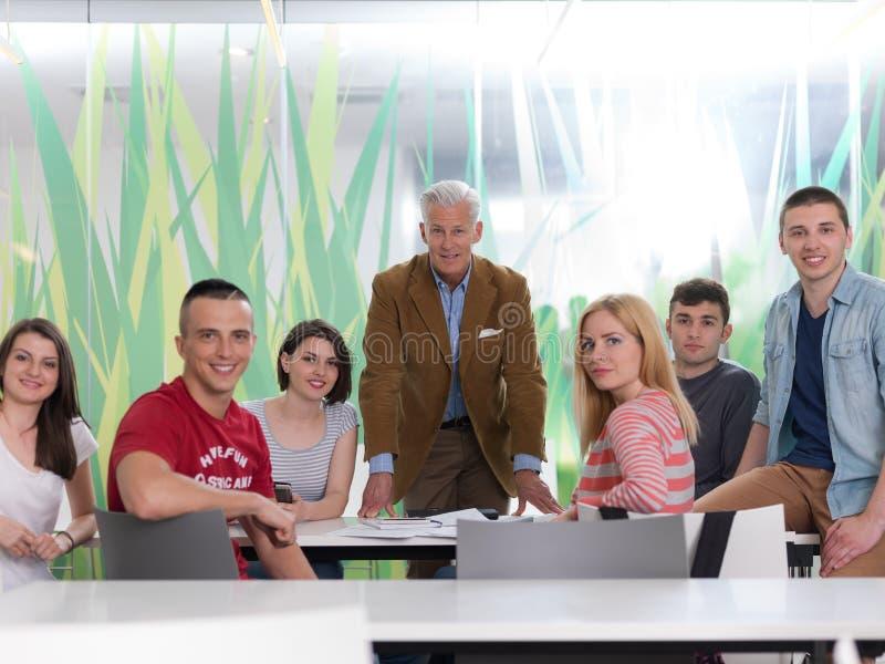 Portret van in leraar in klaslokaal met studentengroep in backg royalty-vrije stock foto's