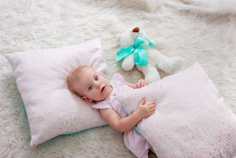 Portret van leuk Europees weinig meisje van de blondeprinses met beer in mooie kleding die op de vloer in verfraaide studio binne royalty-vrije stock foto