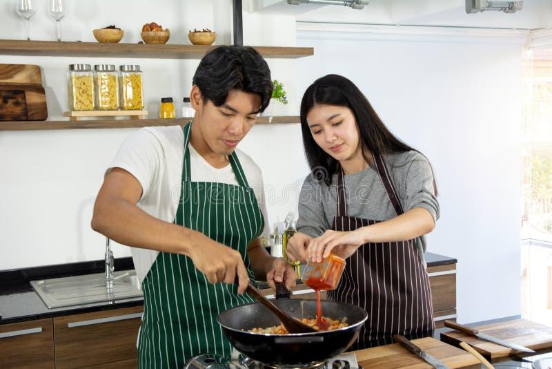 Portret van leuk gelukkig paar die in schort in vrolijke actie ontbijtpaar voorbereiden die intredient in moderne keuken helpen t stock afbeeldingen