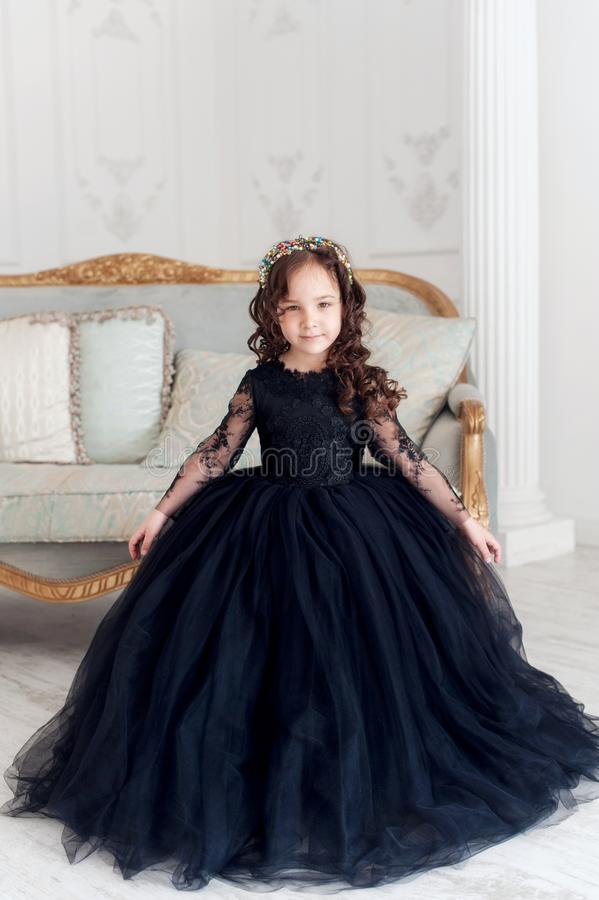 Portret van leuk glimlachend meisje in zwarte prinses pluizige kleding stock fotografie
