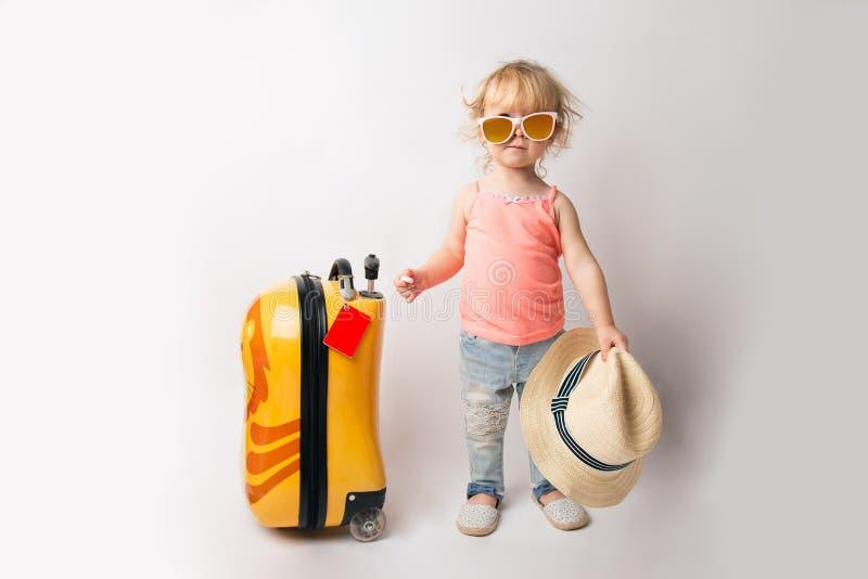 Portret van leuk grappig Kaukasisch babymeisje in de zonnebril van t-shirtjeans met een strohoed in haar handen, een bewegingszie stock foto's