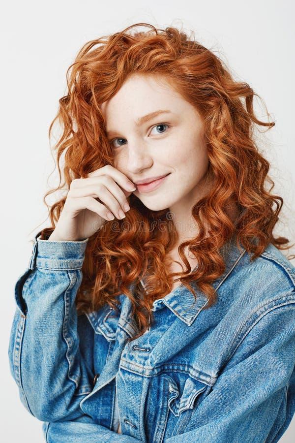 Portret van leuk jong meisje met rood krullend haar en sproeten glimlachen die camera bekijken stock afbeelding