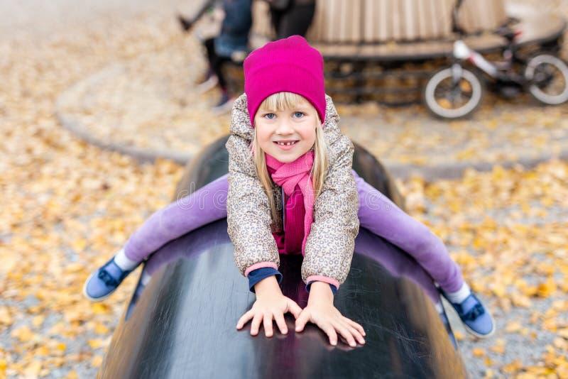 Portret van leuk Kaukasisch blond meisje die pret het spelen hebben bij moderne openluchtspeelplaats bij stadspark in de herfst a stock foto's