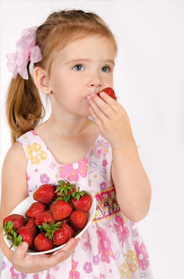 Portret van leuk meisje dat aardbei eet stock afbeelding