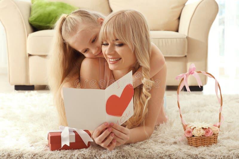 Portret van leuk meisje en haar moeder met met de hand gemaakte kaart thuis stock foto's