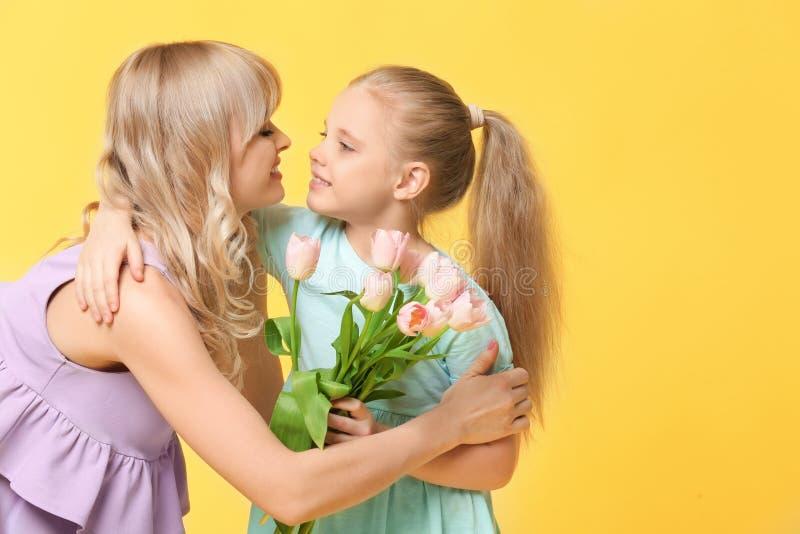 Portret van leuk meisje en haar moeder met tulpenboeket op kleurenachtergrond royalty-vrije stock fotografie
