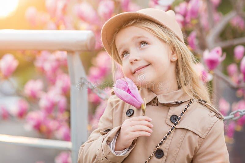 Portret van leuk meisje met blondehaar dat de roze bloem van de holdingshand van magnolia Mening aan het kasteel van de werelderf stock afbeelding