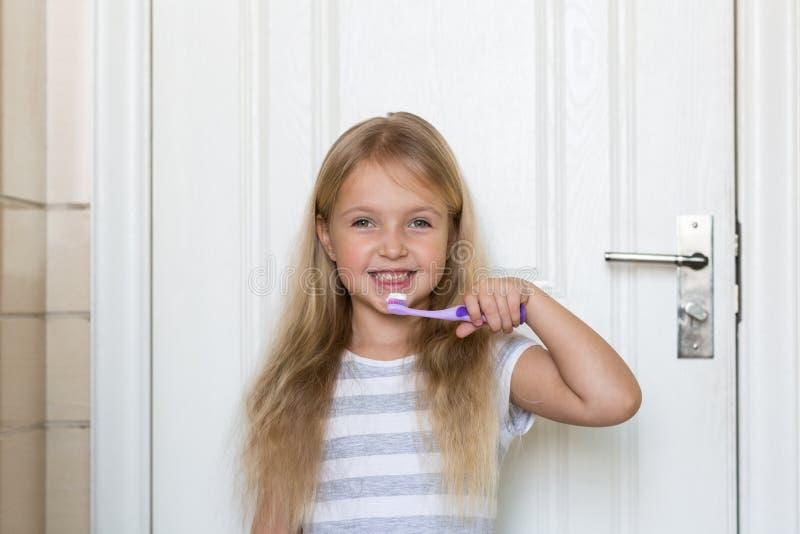 Portret van leuk meisje met blondehaar dat schoonmakende tand met borstel en tandpasta in badkamers royalty-vrije stock foto