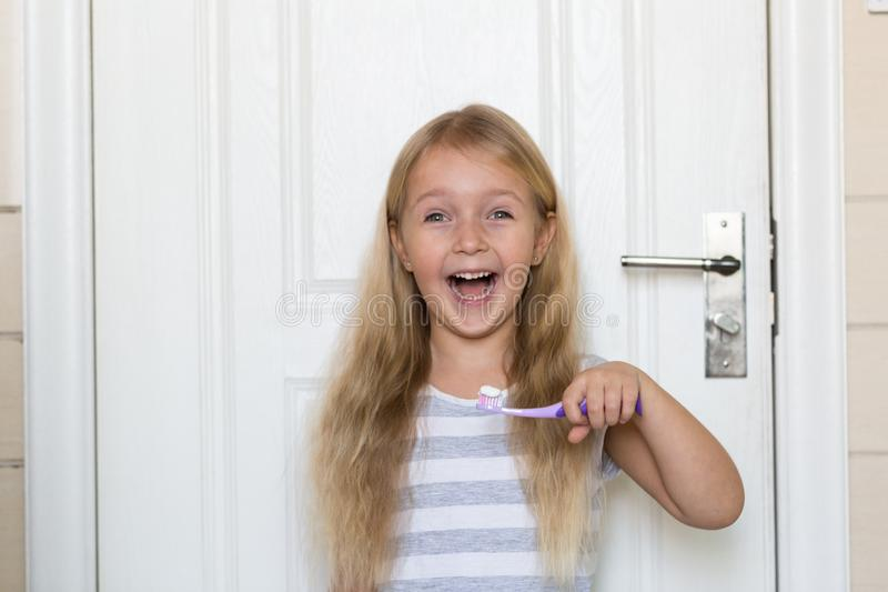 Portret van leuk meisje met blondehaar dat schoonmakende tand met borstel en tandpasta in badkamers stock afbeelding