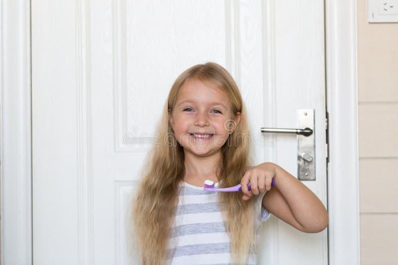 Portret van leuk meisje met blondehaar dat schoonmakende tand met borstel en tandpasta in badkamers royalty-vrije stock fotografie