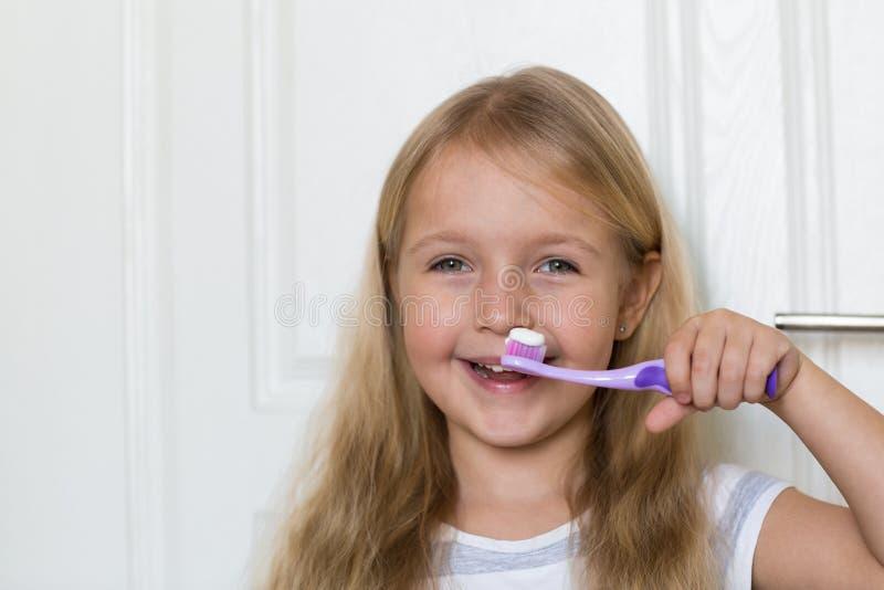 Portret van leuk meisje met blondehaar dat schoonmakende tand met borstel en tandpasta in badkamers royalty-vrije stock afbeelding