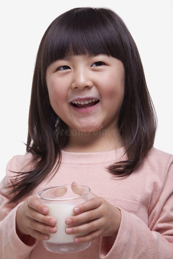 Portret van leuk meisje met klappen die een glas melk met een melksnor drinken stock foto's