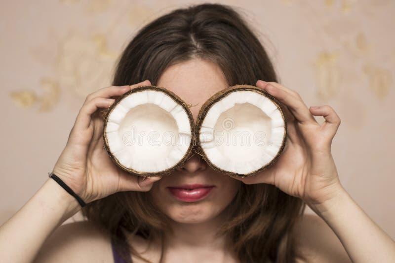 Portret van leuk meisje met kokosnoten in dichtbij haar ogen stock afbeelding