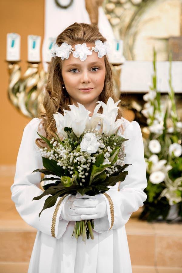 Portret van leuk meisje op witte kleding en kroon op eerste heilige kerkgemeenschap achtergrondkerkpoort royalty-vrije stock foto's