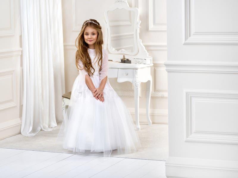 Portret van leuk meisje op witte kleding en kroon op eerste heilige kerkgemeenschap achtergrondkerkpoort royalty-vrije stock fotografie