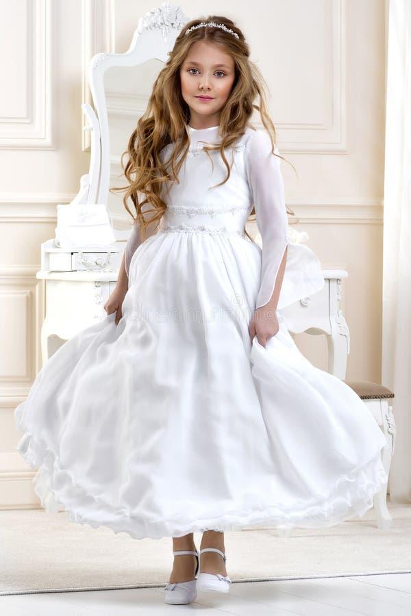 Portret van leuk meisje op witte kleding en kroon op eerste heilige kerkgemeenschap achtergrondkerkpoort stock foto