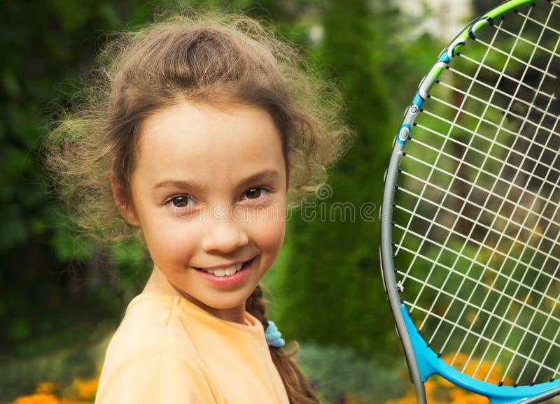 Portret van leuk meisje speeltennis in de zomer stock foto