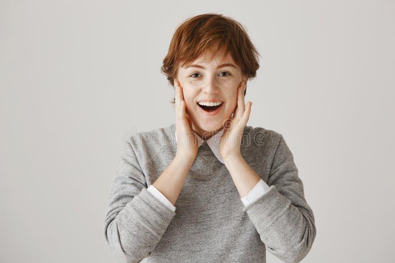 Portret van leuk opgewekt roodharige met kort slordig haar en sproeten die handen op wangen houden en bij camera glimlachen Vrouw stock foto's