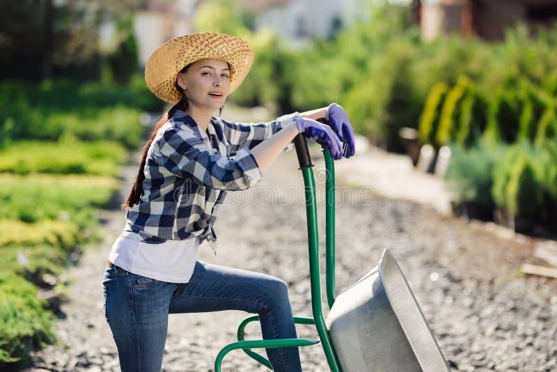 Portret van leuk tuinmanmeisje met kruiwagen die in tuinmarkt werken stock foto