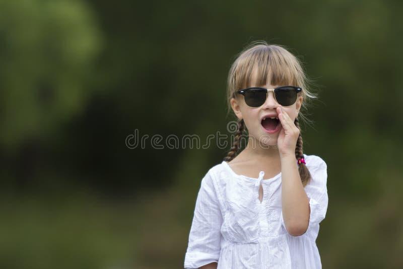 Portret van leuk vrij grappig jong meisje met blonde vlechten in witte kleding en donkere zonnebril stock afbeelding