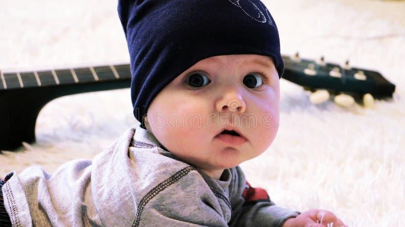Portret van leuk weinig baby en gitaar op witte deken stock foto