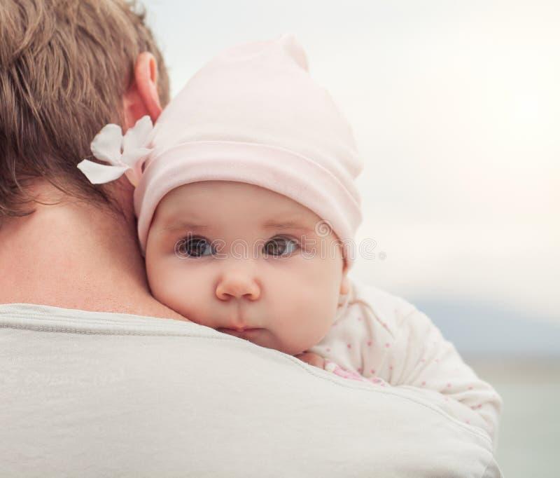 Portret van leuk weinig babymeisje met bloem op vaderschouder in openlucht, ouderlijk zorg en veiligheidsconcept stock foto's