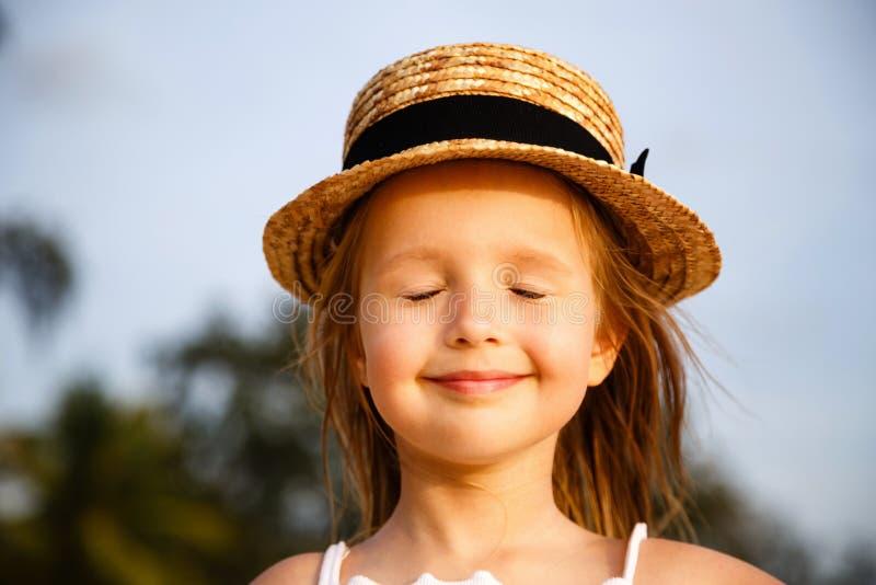 Portret van leuk weinig blondemeisje in strohoed met gesloten ogen openlucht Gezichtsclose-up, lachebekje, waar geluk royalty-vrije stock fotografie