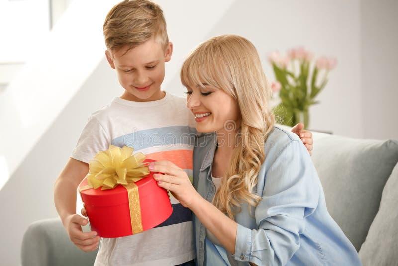 Portret van leuk weinig jongen en zijn moeder met giftdoos thuis stock afbeeldingen