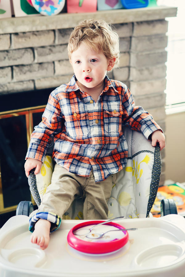 Portret van leuke aanbiddelijke Kaukasische de jongen van het kindjonge geitje status als hoge voorzitter met been op lijst vroeg stock foto's